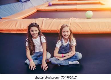 Little pretty girls having fun outdoor. Sitting on trampoline in children zone. Amusement park