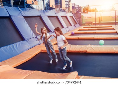 Little pretty girls having fun outdoor. Jumping on trampoline in children zone. 