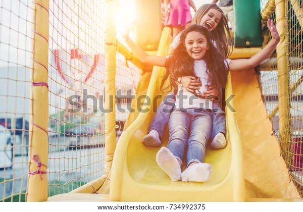 Little pretty girls having fun outdoor. Playing in children zone in amusement park.