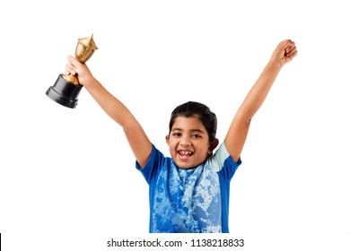 little pretty indian/asian girl with an award, holding a trophy with success and proud expression, isolated over white background