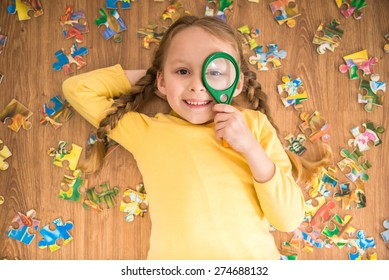 Little pretty smiling girl in yellow  pullover laying on the floor and playing with puzzle and loupe.