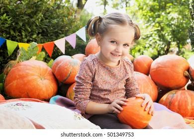 Little princess cute girl with a pumpkin in her hands. Joyful girl.  Stylish pretty little girl sitting among a lot of pumpkins.