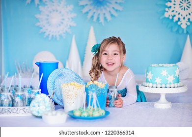 Little princess girl on a styled Frozen birthday party with snowflakes cakes