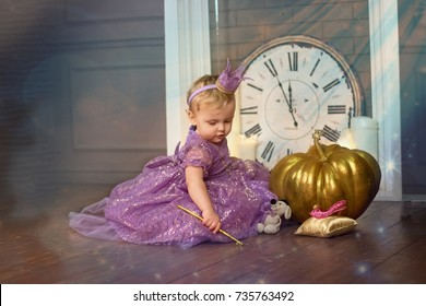 Little princess sitting near magic pumpkin and holding a magic wand in the hands of. Fairy tale. Soft focus.