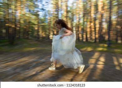 Little princess wallks in an evening dress in a summer forest, natural light