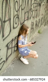 Little puberty girl squat in city street and lean on graphite designed wall. Urban photo