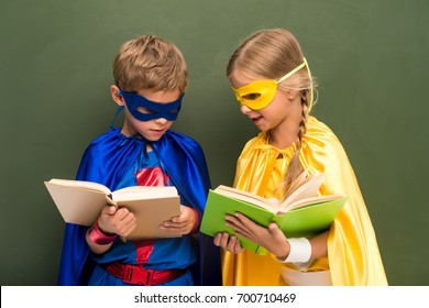 little pupils in superhero costumes reading books, chalkboard behind