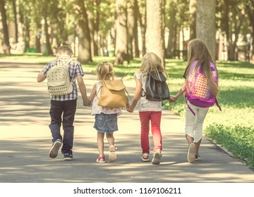Little pupils walking home from school across the sunshine park