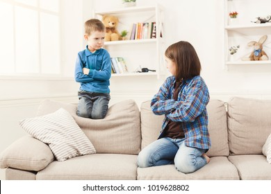 Little quarrel. Small pretty girl and her brother offended, sitting on couch at home with hands crossed and displeased faces