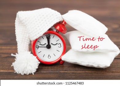 little red alarm clock in a nightcap with cushions on a dark wooden background