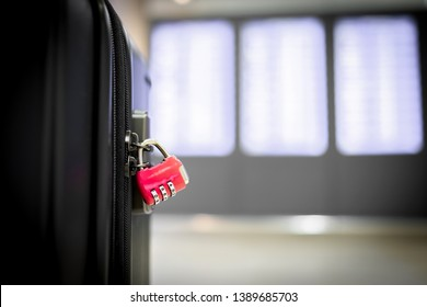A little red combination padlock locking zippers on luggage in airport terminal. Copy space for text.