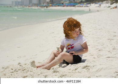 A little red headed girl with ringlets in her hair  playing alone in the sand on the beach in Florida.