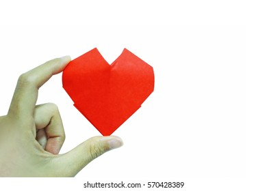A little red heart is held by a little hand on white background