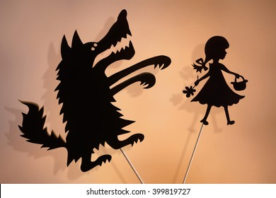 Little Red Riding Hood and the Big Bad Wolf shadow puppets and their shades on the soft glowing screen of shadow theater.