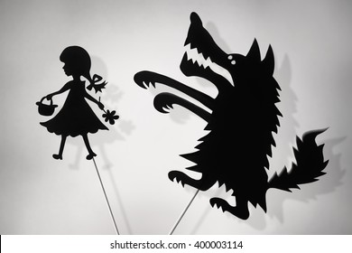 Little Red Riding Hood and the Big Bad Wolf shadow puppets and their shades, copy space background.