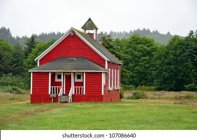 Little red schoolhouse in meadow on misty morning