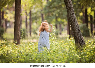 Little red-hair girl walk on sunny green lane in park. Foxy hair toddler run through high grass in the magic summer sun light, having fun carefree happy childhood