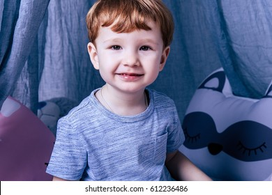 Little red-haired boy with brown eyes in a child's cot, childhood