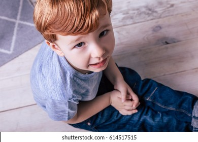 Little red-haired boy with brown eyes, child, childhood, crawling on the floor playing on the floor