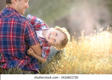 A little red-haired boy in his father's arms. Hugging on a cliff overlooking the sea.