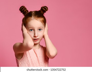 Little red-haired child girl covers her ears with hands, dressed in a dress, on a pink background.