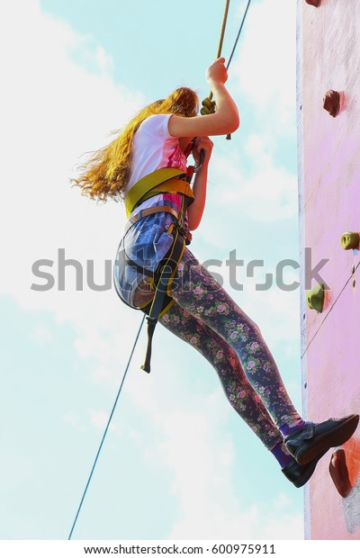 Little red-haired girl climbing a rock wall