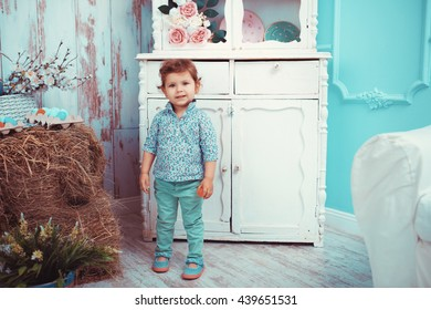 The little red-haired girl playing in the room with the spring interior. The concept of happiness, joy and family values