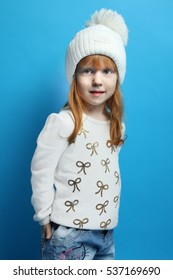 The little red-haired girl posing in a white sweater and hat. The concept of children's fashion, winter.