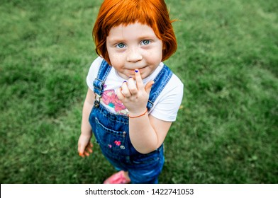 Little red-haired girl stands on the green grass and holds an inquiring finger. Clothing and hairstyle reminiscent of Carlson from a fairy tale and cartoon. Beautiful and mysterious smile. European.