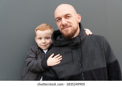 Little red-haired son hugs dad on a gray background, dressed in black and gray clothes