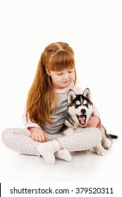 Little redhead girl with a puppy husky