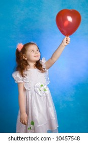 Little redhead girl with red balloon on blue background