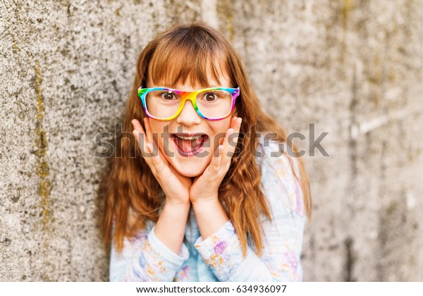 Little redhead girl wearing rainbow eyeglasses. Hands on cheeks looking at the camera with astonished or shocked expression, mouth wide open. Human facial expressions. Back to school concept