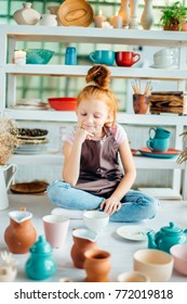 little redhead girls sitting in lotus pose in studio are made of ceramic cups