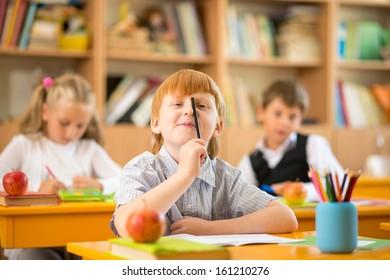 Little redhead schoolboy behind school desk during lesson