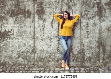 Little rest. Full length of beautiful young woman looking away with smile while standing against concrete background outdoors