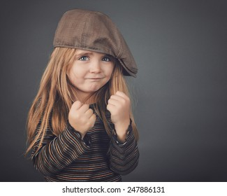 A little retro girl with a hat has her fists up and looks strong and tough on a gray background for a safety or strength concept.