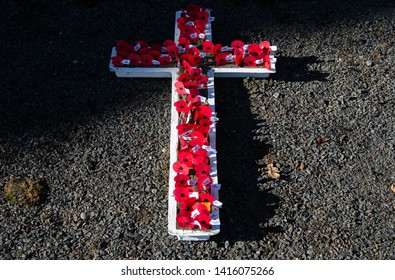 LITTLE RIVER, NEW ZEALAND - APRIL 25: White wooden cross with red poppies decoration following the remembrance War hero service on Anzac Day April25, 2019 at Little River's War Memorial, New Zealand.