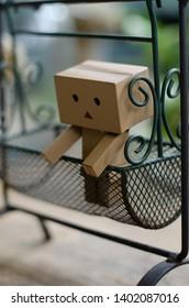 Little robot character Danbo. A cute danbo board on a swing in the garden