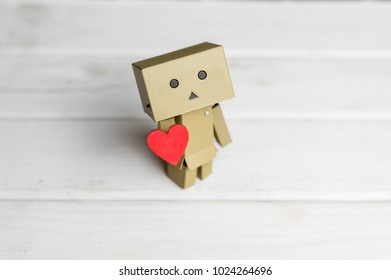 Little robot character Danbo standing on wooden floor with red heart in hand