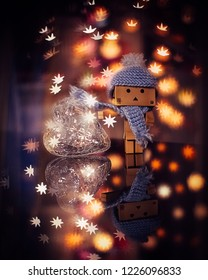 Little robot toy character Danbo wearing hat and scarf holding heart with reflection. Perfect  post card design, Holiday concept, magical loving  atmosphere