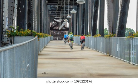 Little Rock, AR—May 22, 2018; bikers ride on the William Clinton Presidential Bridge across the Arkansas River. The Bridge is a former Union Pacific railroad bridge retired in 1980.