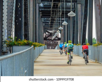 Little Rock, AR—May 22, 2018; pack of bikers ride across the president Clinton bridge.  The Clinton bridge is a bike and pedestrian span crossing the Arkansas river.