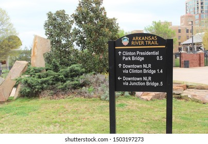 Little Rock AR/USA: March 28, 2018 – Arkansas River Trail sign shows distances to Clinton Presidential Park Bridge and to downtown. The 88 mile Trail showcases diverse geographies of central AR.