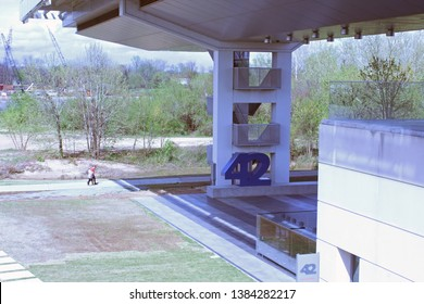 Little Rock, AR/USA: March 29, 2018 – Blue numerals for restaurant at ground floor of Clinton Library called 42 Bar and Table with views of Arkansas River. Pedestrians walking along river in distance.