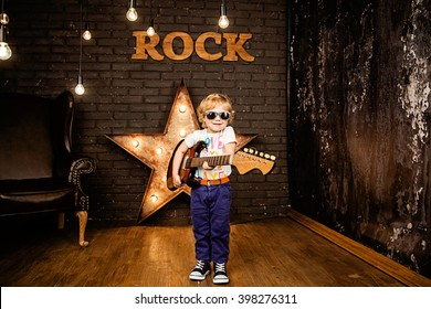Little rock girl with guitar. Cheerful little girl playing electric guitar on grunge background.