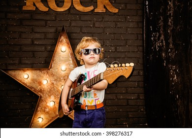 Little rock girl with guitar. A very serious girl plays the guitar and dreams of becoming a rock star grunge background