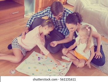 Little russian girls playing with parents at board game on floor