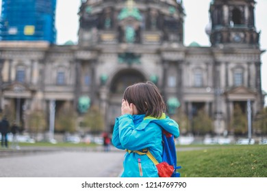 Little sad boy with backpack covered his face with hand sitting with Berlin cathedral (Berliner dom) background.he tired or get lost from travel