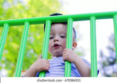 Little sad boy behind a fence.. Child concept.